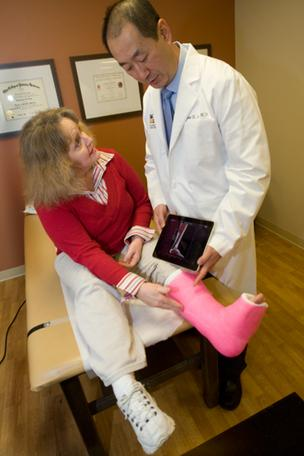 Dr. Thomas Lee, an orthopedic surgeon at the Foot and Ankle Center, uses an iPad to discuss treatment for a stress fracture with patient Trena England.