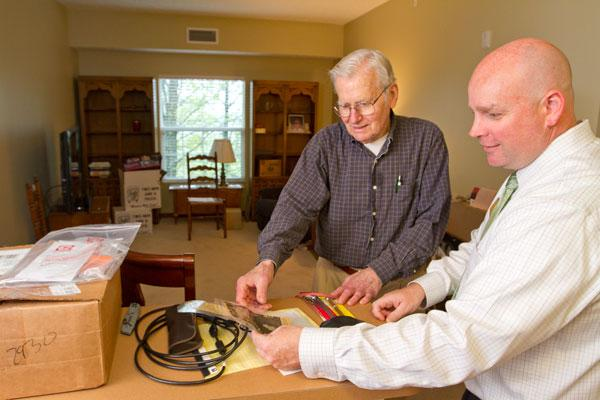 Tom Chael recently moved into Parkside Village, a senior living community in Westerville. He's pictured unpacking some of his belongings with Executive Director Scott Van De Water, right.