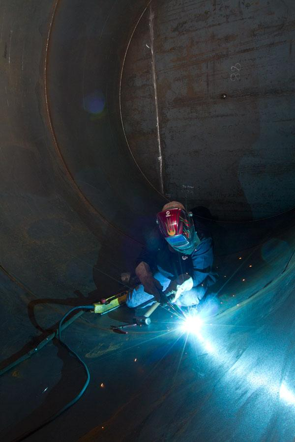 Shane Vest welds steel plates to make a storage tank used at drilling sites. Westerman Cos. was acquired by Worthington Industries last year.