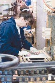 Diane Hopkins assembles a washboard.