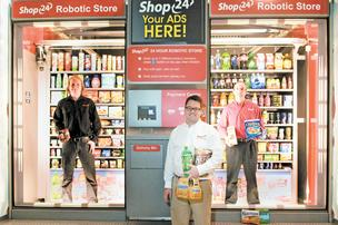 Shop24's Matthew Reckner, center, enlists the support of two colleagues to show off the scale of the company's vending machines, which can handle products from just about any aisle in a traditional grocery store.