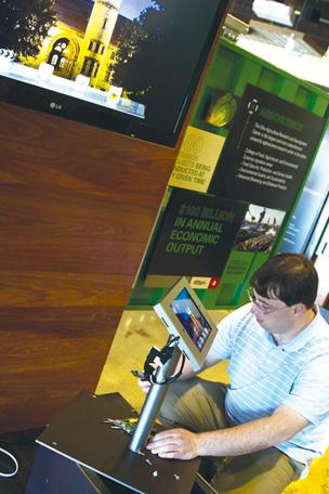Mike Coutinho installs displays in the lobby of Ohio State's technology commercialization office at the South Campus Gateway designed to show visitors the kinds of research being undertaken at the university.