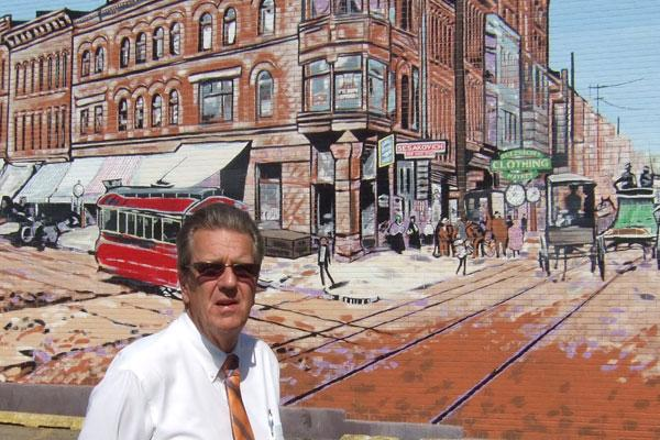 Progress Alliance Executive Director Ed Looman, framed by one of the many murals in Steubenville's downtown, is trying to ensure the economic benefits from shale drilling provide lasting benefits for the city and the rest of Jefferson County.