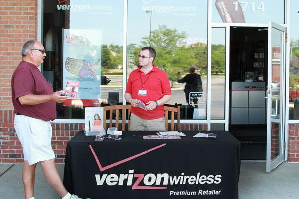 With his Pickerington Verizon store left in the dark, Manager John Betts set up outside to talk to customers about phone plans, even if he couldn't sell anything. Whitehall resident Dan Espinoza also was without power.