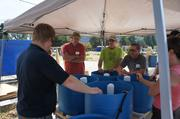 Jason Garvey, pictured at left with his back to the camera, explains the components of an aquaponics system at a workshop.