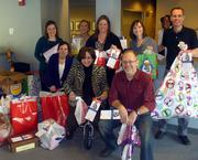 Employees of the Munsch Hardt Kopf & Harr, P.C  law firm and CASA volunteers recently delivered gifts to CASA for 50  children and four families who were adopted by the firm this year.