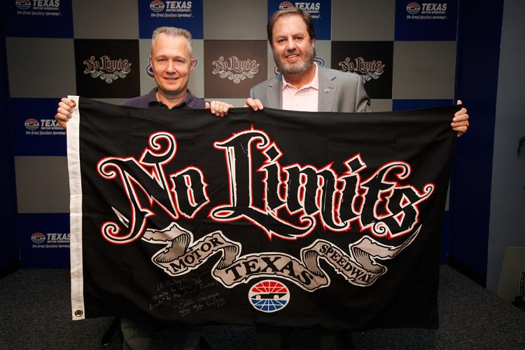 NASA astronaut Doug Hurley and Texas Motor Speedway President Eddie Gossage show the flag that Hurley took into space aboard the Shuttle Atlantis.