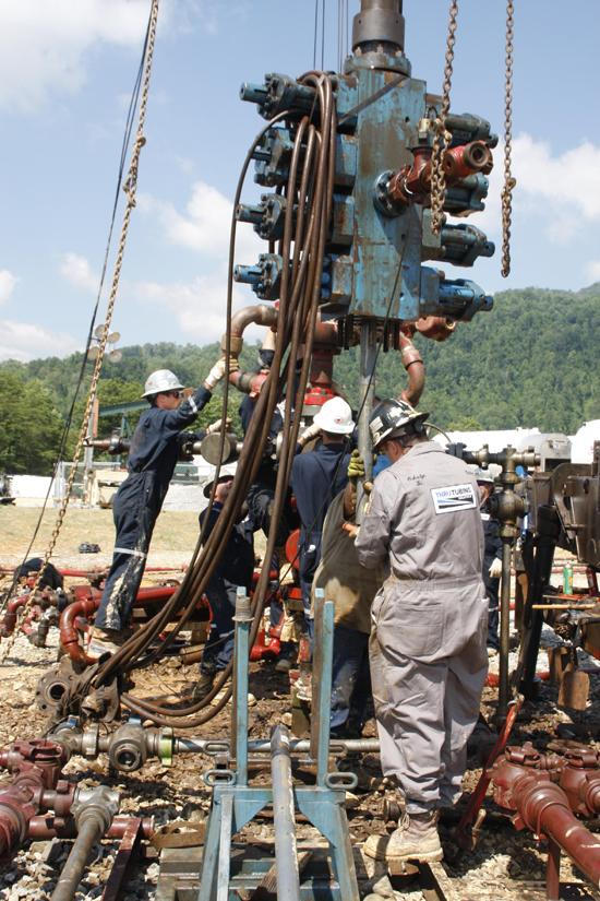 Contractors work at an Atlas Energy Inc. well site in the Marcellus Shale. Chevron Corp.completed its acquisition of Atlas in February 2011.