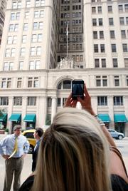 Skyler Baty takes a cellphone photo of the Adolphus Hotel while Mike Wyatt and Mark Lea wait to continue their walk.