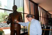 Mike Wyatt pauses at a statue of the late H.L. Hunt at Thanksgiving Tower in downtown Dallas.