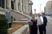 Mike Wyatt, Skyler Baty, Kirby White and Mark Lea read the historical marker outside the old Municipal Building.
