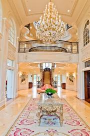 A chandelier hangs over a long entry that leads to the grand stair case at Champs d'Or in Hickory Creek.