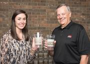 "In celebration of Acme Brick's anniversary, the company gave each of its employees a ""birthday present"" of four clear tumbler glasses with different photographic images of events in Acme's history. From left: Laura Fanta, in Acme's HR department, and Dennis Knautz, president and CEO."