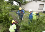 Pike Electrical employees help to return power to to residents on McLarty Street in Dallas following the April 3 storms.