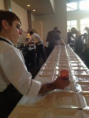 A server prepares plates for the first course of the night.