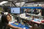 Technician Danielle Dunlap cleans and refurbishes game controllers with the help of Mario.