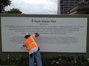 A worker cleans a wall with donor names at Klyde Warren Park.