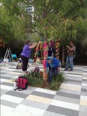 A group of people were yarn bombing trees in the park Thursday afternoon.
