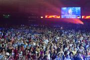 Country singer Rodney Atkins is projected on a screen while the crowd watches him live on stage.