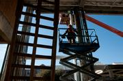 A worker rides toward an elevated position at the College Park development at the University of Texas at Arlington.