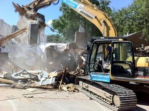 Dr. Tyler Cooper operates an excavator to help tear down the old Cooper Fitness Center.