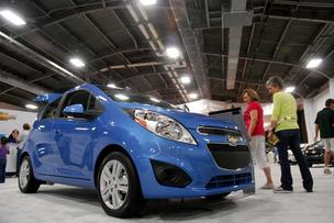 Fair goers check out a Chevrolet Spark at the State Fair Auto Show. The subcompact starts at a retail price of a little more than $12,000.