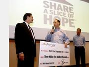 "Kurt Kane, center, chief marketing officer of Pizza Hut, presents a  check for $3.2 million to Rick Leach, president and CEO of World Food Program USA. Pizza Hut's donation was the largest in the history of its ""Week of Giving"" program."
