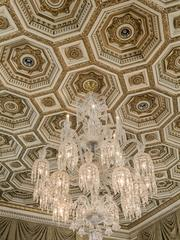 The chandelier is featured with an ornate gold ceiling.