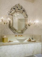 An ornate mirror overlooks the one of the bathroom vanities at 9806 Inwood Road.