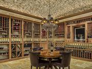 The wine cellar features walls of wine storage.