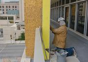 A workman replaces gold tiles on a column at the Continental Building.