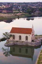 The McKinney development includes a chapel surrounded by water.