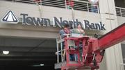 Workers place Town North Bank sign on the side of Centura Tower I off 