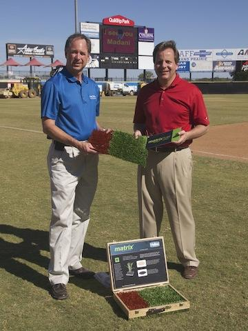 Tim Shinogle (left) of Grand Prairie Parks & Recreation Department, and Scott Berry, president of the Grand Prairie AirHogs, with samples of the turf that's being installed at QuikTrip Park.