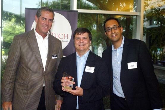 "Vance McCollough of TravisWolff, left, and Vik Thapar, right, director at North Texas Regional Center for Innovation & Commercialization, present the ""One To Watch"" award to Rob Langhorne, CEO of Cloudlogix."