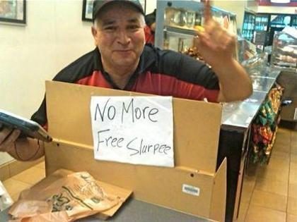 A 7-11 employee in New York signals his store is out of free Slurpees