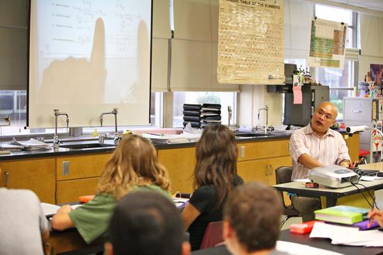 Dallas ISD teacher Rachmad Tjachyadi works with students in an Advanced Placement class at W.T. White High School. Students may be rewarded for strong scores on A.P. exams.