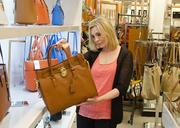 Melissa Hammond examines a Michael Kors handbag at the Belk store in McKinney. The department store chain plans a wider selection of luxury brands at its Dallas flagship store, scheduled to open in spring 2014.