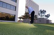 Maximizing value: David Pettle, executive vice president of the office division at Dallas-based Lincoln Property, enjoys the new putting green in the upgraded green space on the plaza at Energy Square.