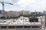 Old and new: The existing Parkland Memorial Hospital campus, a labyrinth of buildings, is visible from the parking garage of the new facility, still under construction.