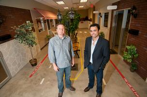Robert Baker and Nathan Hanks stand in a hallway in ReachLocal's space in Plano.
