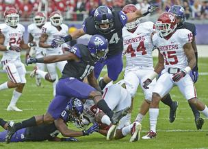 Members of the TCU special teams shut down a punt return by Oklahoma. The Horned Frogs will play Dec. 29 in the Buffalo Wild Wings Bowl for a $3.35 million postseason payday for the school.
