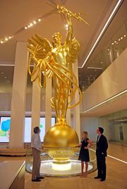 "Mike Wyatt, Skyler Baty and Mark Lea admire ""The Spirit of Communication,"" a 28-foot bronze statue in the lobby of AT&T's headquarters building in downtown Dallas."