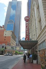 The Urban Armadillos walk under the awning at the Majestic Theatre, which is the last of its kind remaining in downtown Dallas.