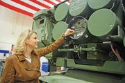 Becky Withrow, manager of Business Development for Tactical Missiles/Combat Maneuver Systems for Lockheed Martin, checks out the controls at the rear of the missile pod on a Multiple Launch Rocket System at Missiles and Fire Control's Grand Prairie facility.