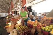 Olga Cabrera works a produce booth at the Dallas Farmers Market.