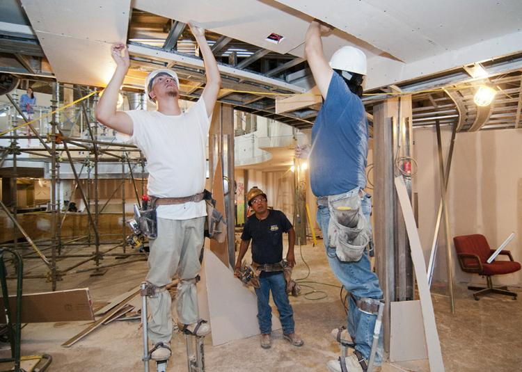 KITCHEN PREP WORK: Roberto Sandoval, Florente Arellanes and Jose Sandoval help to build the Sub-Zero Wolf showroom, which will include staged kitchens and a large theater kitchen.