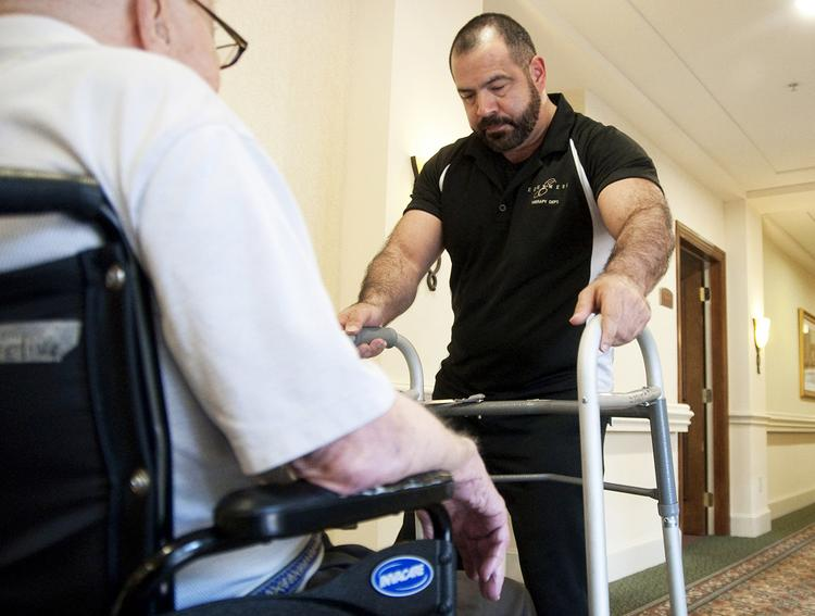 Doing more with less: Physical therapist John Barron works with a resident at the Edgemere retirement community in Dallas, which has factored a 2 percent to 3 percent reduction in Medicare reimbursements into this year's budget.