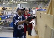 GM employee Chris Brown instructs Arlington Voice reporter D.J. Zitko on the simulated work environment assembly line.