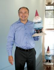 Carl Sparks, CEO of Travelocity, with the company's trademark gnome. Sparks says he's got roughly 100 jobs worldwide he needs to fill.